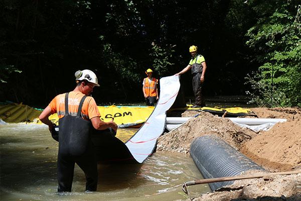 Il tubo flessibile di scarico DP-3075, di 450 mm di diametro, è collegato allo sbarramento Water-Gate ©. Quindi stendiamo completamente a valle prima di riempire l'acqua.