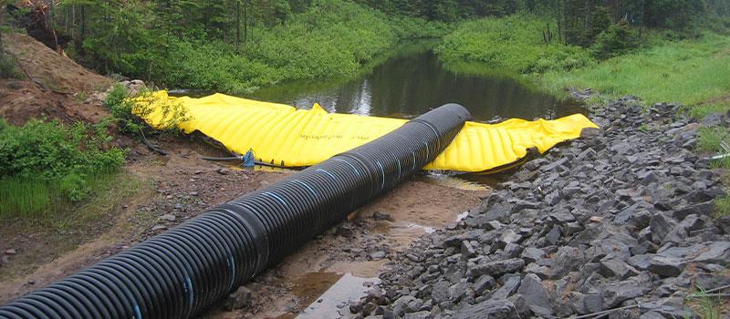 Cassette flessibili Water-Gate © per lavori nei fiumi. Diga smontabile con by-pass tramite conduttura.