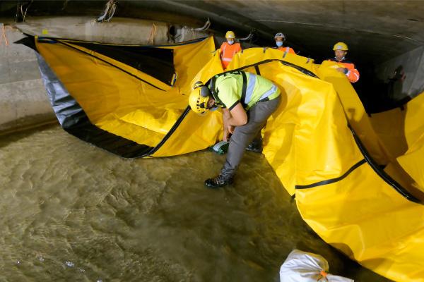 Posizionare sacchi di ghiaia sul terreno sotto la diga flessibile Water-Gate © per aumentare le forze di attrito.