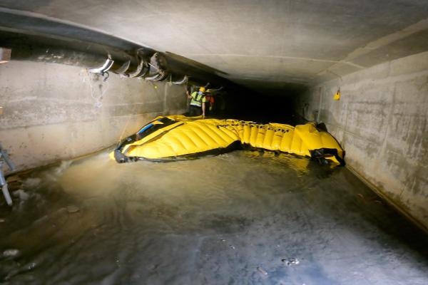 Rimozione di una cofferdam flessibile Water-Gate©. Il bordo d'attacco viene sollevato per far passare l'acqua sotto il cassero e ridurre le forze di attrito.